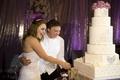 Bride and groom cut white cake with rhinestones