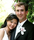 Bride wearing a diadem and diamond drop earrings and groom in tuxedo with silver tie and orchid