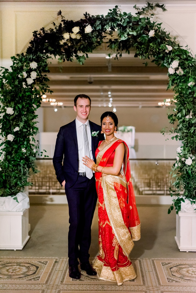 south asian bride in red lehenga choli with gold details, groom in navy suit