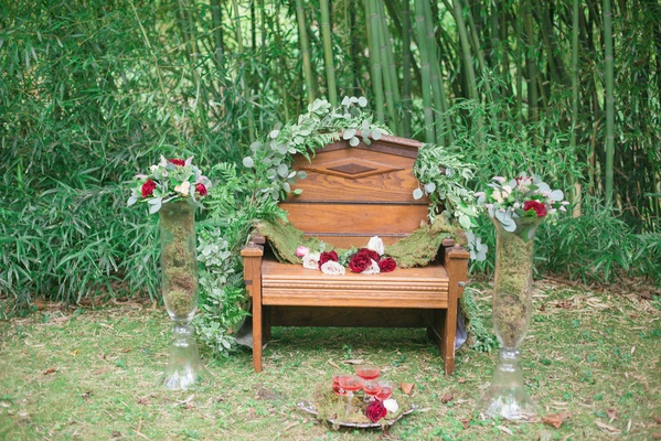 wooden bench vines green red blush flowers tall vases outdoor celtic wedding