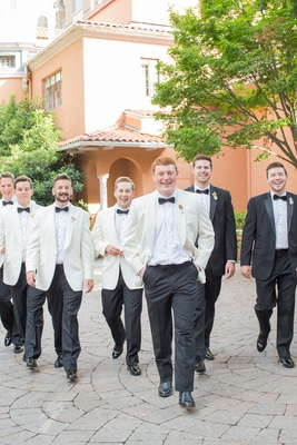 Groom in ivory suit jacket and black bow tie with matching groomsmen tuxedo shoes
