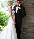a bride and groom look lovingly at each other during their first look bride in monique lhuillier