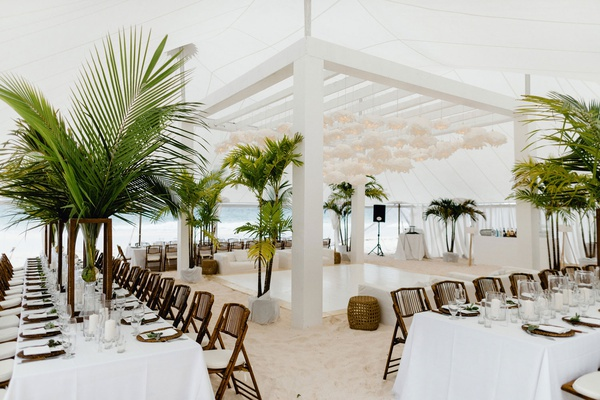 wedding reception on white sand beach bahamas tropical decor green palms white paper lanterns decor