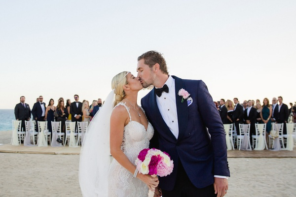 Sheldon Souray and Barbie Blank kiss at end of aisle after wedding ceremony on the beach in Mexico