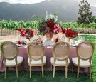 pink table linens red dark purple floral arrangements and gold and tan chairs rustic wedding