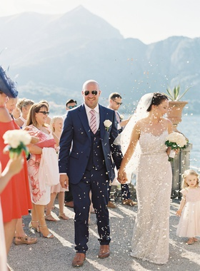 wedding guests tossing confetti flower petals as bride and groom arrive to reception venue lake como