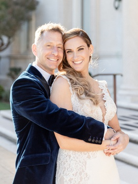 groom in navy velvet suit jacket hugging bride in pnina tornai from behind
