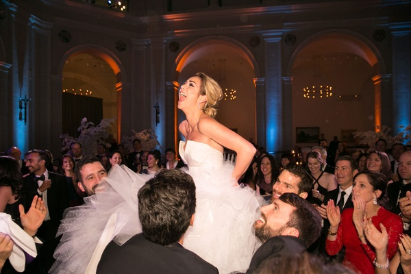 Bride on chair during hora at jewish wedding in brooklyn at museum venue
