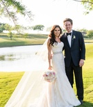 Bride in Monique Lhuillier lace dress and long veil white pink bouquet long hair curled groom