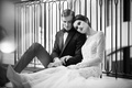 wedding styled shoot, model in lace ines di santo gown leans head on male model, black and white
