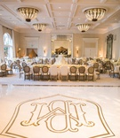 upside down view of custom white dance floor with gold monogram outline pattern