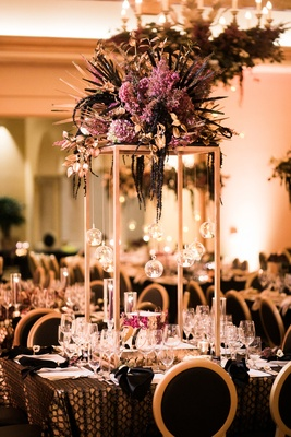 rectangular structure with purple flowers and palm fronds on top, unique centerpieces