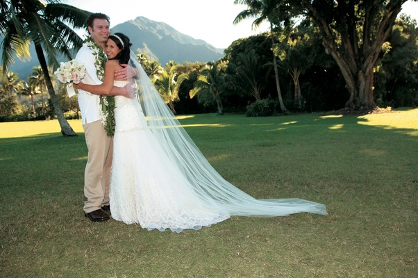 bride and groom in casual island outfit in filed overlooking mountain