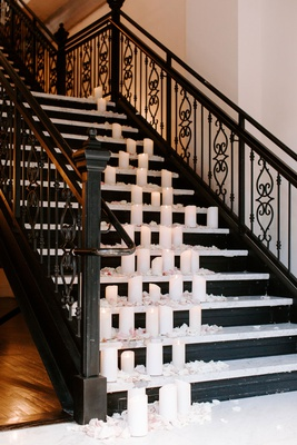 clack staircase with white flower petals and lots of pillar candles