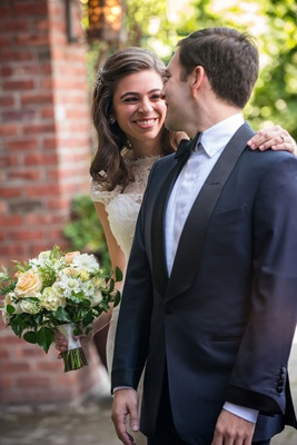 Groom in navy blue tuxedo with black lapels and bride in lace wedding dress bouquet first look