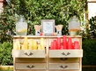 wedding ceremony outside dresser with yellow red cups fun straws peach decor water dispenser