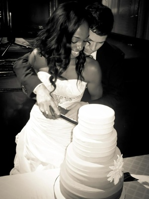 Black and white photo of Enuka Okuma cutting wedding cake