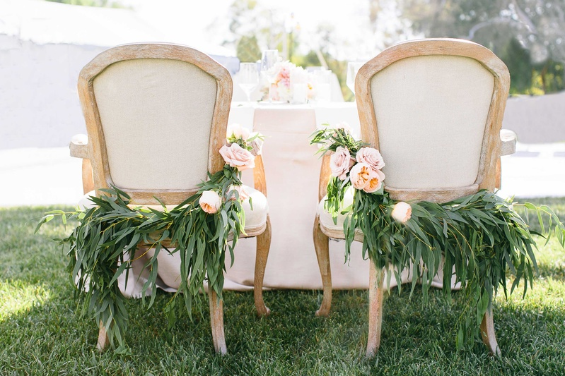 a couples chairs at their sweetheart table for their reception featuring lush greenery light flowers