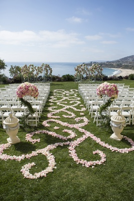 Grass lawn ceremony with pink flower petals and white chairs