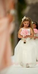 Flower girls in white dresses walking down aisle