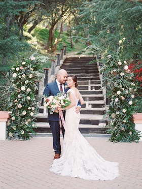 wedding portrait bride and groom outdoors loose bouquet navy blue suit brown dress shoes
