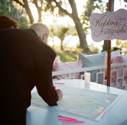 Wedding guests signing custom map with pink