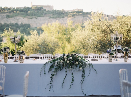 wedding reception outdoor italy destination white head table greenery cascading vines umbria candles