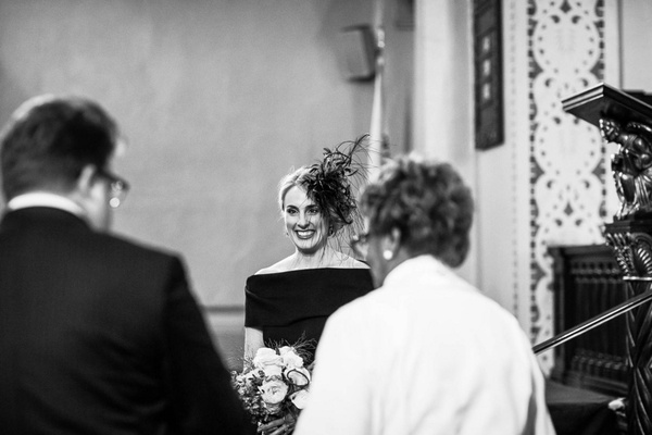 Black & white photo of bride in an off-the-shoulder black dress, feather headpiece at altar, groom
