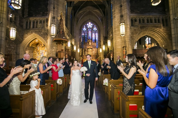 Bride and groom walk up church wedding aisle