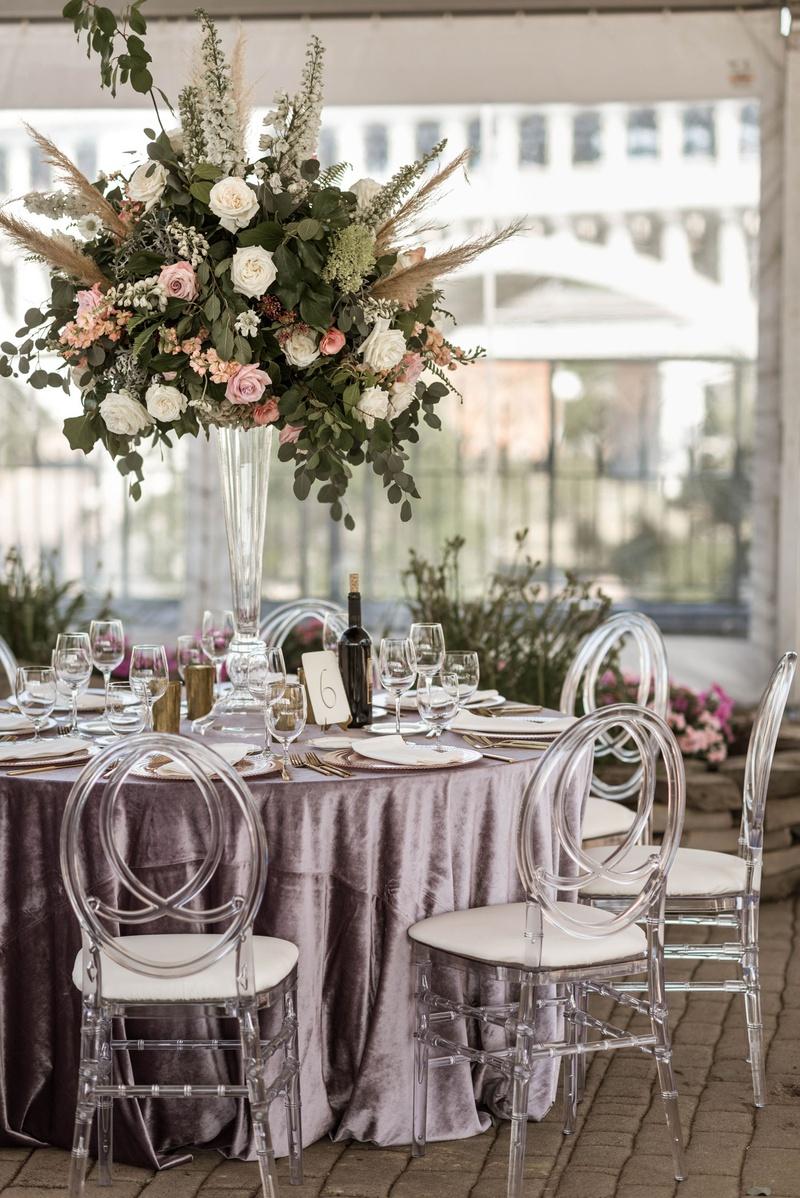 boho chic wedding reception clear tent velvet purple linen acrylic oval chair tall centerpiece
