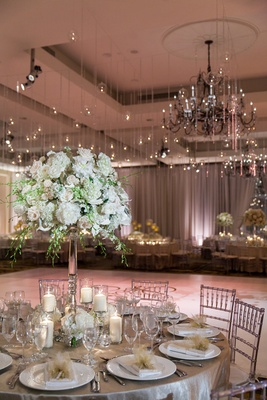 silver tablescape underneath hanging lights edison bulbs crystals dance floor wedding chandelier