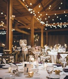 Wedding reception with confetti table number gold candleholders and wine glasses and twinkle lights