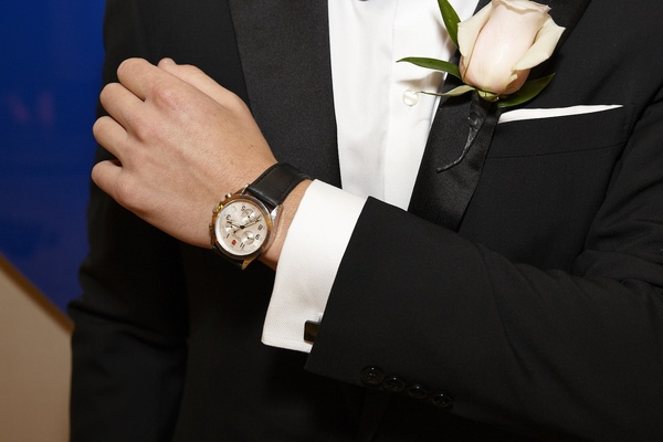 Groom in black tuxedo with blush rose on lapel