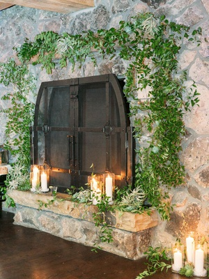 stone fireplace surrounded by greenery and with candles