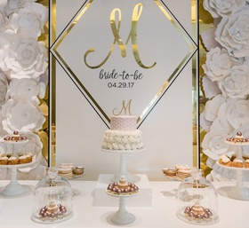 The magnificent dessert display of sweet treats with a custom backdrop of gold etched wall panels pe