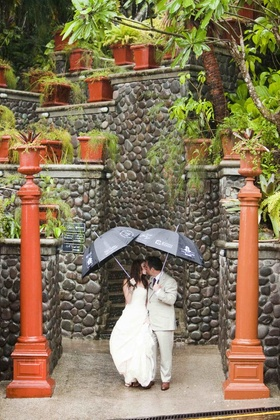 Bride and groom kissing under umbrellas