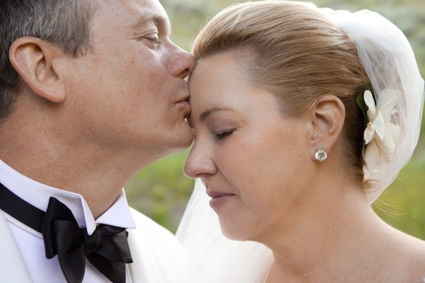 Groom kisses bride's forehead on wedding day