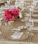 Wedding reception table with gold sequined tablecloth and white and pink flowers