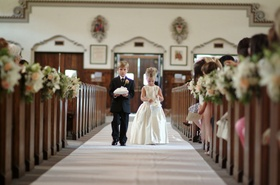 Flower girl and ring bearer walk together down aisle