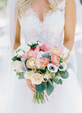 bride in mark ingram atelier wedding dress with bouquet peach pink orange blue green flower anemone