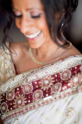 Bride in a white sari with burgundy and gold embroidery accessorizes with gold earrings and necklace