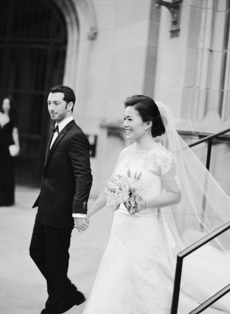 Black and white photo of bride and groom smiling as they leave church wedding ceremony
