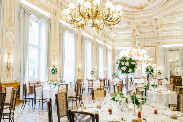 classic wedding color palette for villa ballroom reception chandelier candelabra cane back chairs