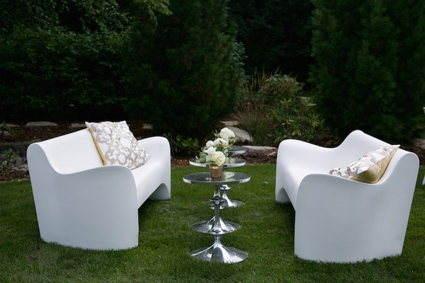 White modern sofas with silver side tables and pillows