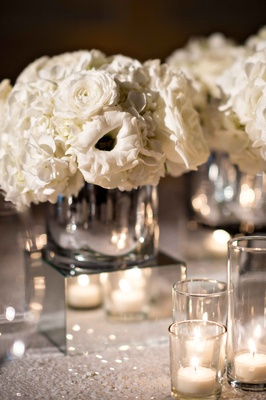 Small white flower centerpiece on mirror cube with sequin table linen