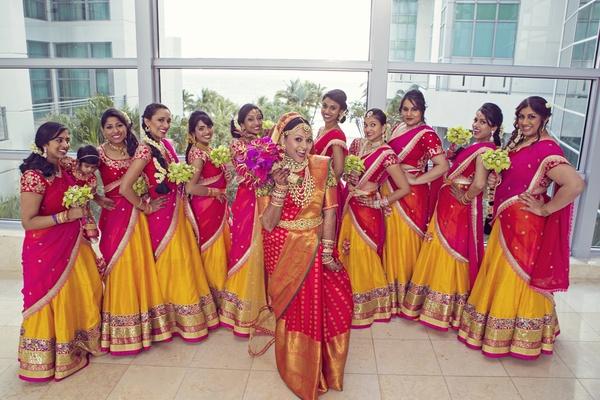 Indian wedding, bride and bridesmaids in traditional sari, red, gold, orange saris, fun bridesmaids