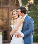 bride in mira zwiliinger wedding dress long blonde hair groom kiss on cheek blue suit yellow tie