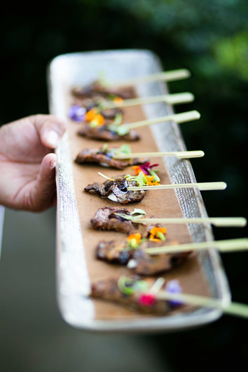 Wedding cocktail hour appetizer beef on toothpick skewer with edible flower