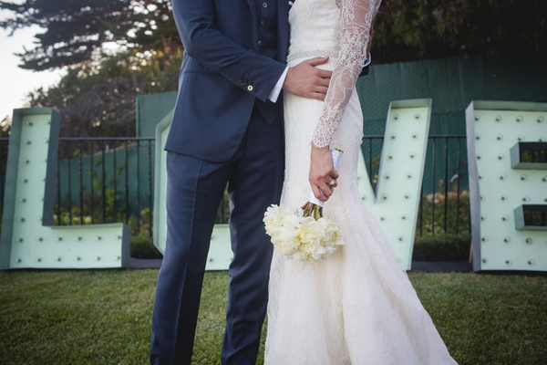 Bride and Groom pose at wedding venue, lace white mermaid dress