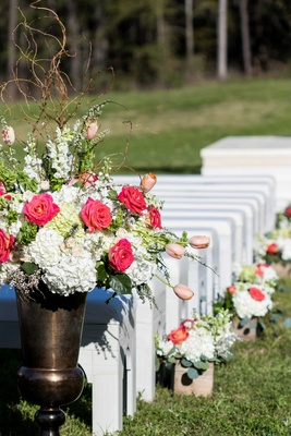 White benches at outdoor ceremony with boxes and urns of white hydrangea and pink flowers